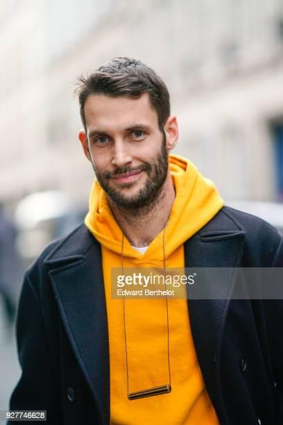 Simon Porte Jacquemus wears a yellow hoodie sweater a black jacket large pants white sneakers shoes outside APC during Paris Fashion Week Womenswear...