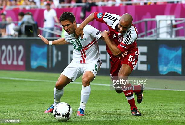 Simon Poulsen of Denmark and Joao Moutinho of Portugal tussle for the ball during the UEFA EURO 2012 group B match between Denmark and Portugal at...