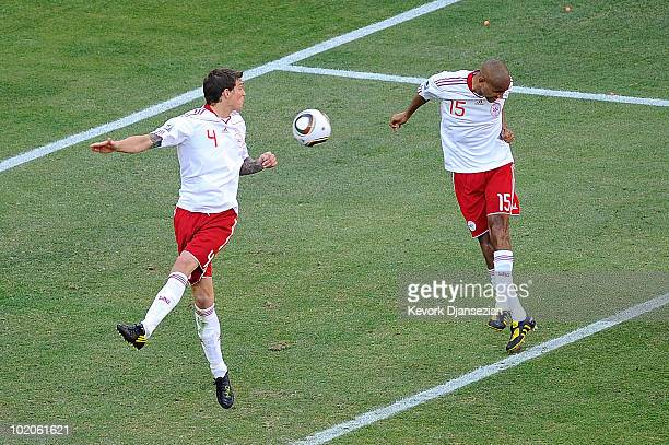 Simon Poulsen of Denmark heads the ball which deflects off Daniel Agger and goes into the net during the 2010 FIFA World Cup Group E match between...