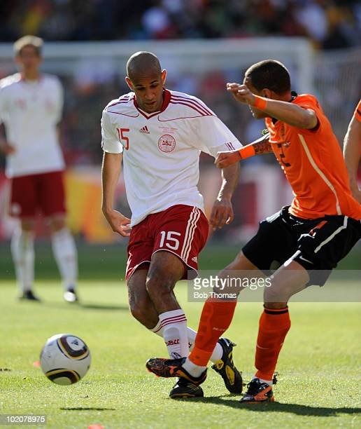 Simon Poulsen of Denmark is tackled by Gregory Van Der Wiel of the Netherlands during the 2010 FIFA World Cup Group E match between Netherlands and...
