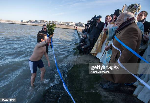 Simon Prokopczyk retrieves a crucifix from the sea during a traditional Greek Orthodox blessing at Margate beach for the Feast of the Epiphany on...