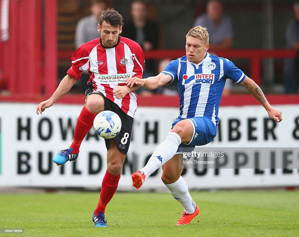 Simon Richman of Altrincham tangles with Martyn Waghorn of Wigan Athletic during the pre season friendly between Altrincham and Wigan Athletic at the J Davidson stadium on July 14, 2015 in Altrincham, England.
