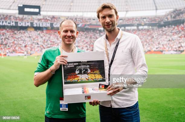 Simon Rolfes is given a gift by the National Team Fan Club during the international friendly match between Germany and Saudi Arabia at BayArena on...