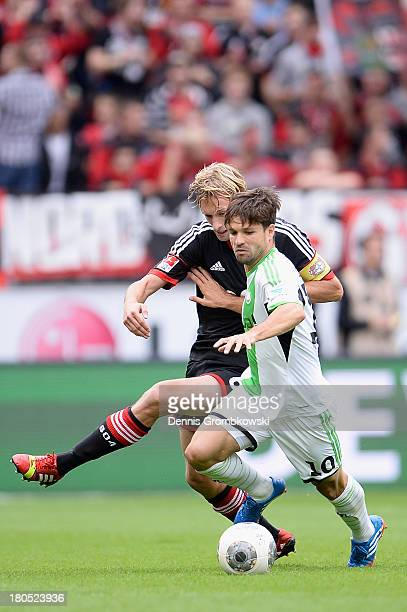 Simon Rolfes of Bayer Leverkusen challenges Diego of VfL Wolfsburg during the Bundesliga match between Bayer 04 Leverkusen and VfL Wolfsburg at...