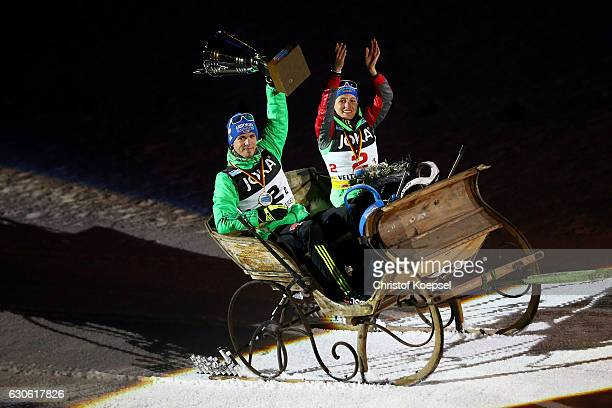 Simon Schempp of Germany and Vanessa Hinz of Germany lift the winning trophy during a lap of honour in a carriage after winning the JOKA Biathlon...