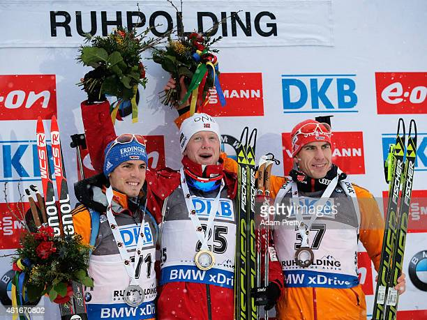 Simon Schempp of Germany second place, Johannes Thingnes Boe of Norway first place and Arnd Peiffer of Germany third place celebrate on the podium...