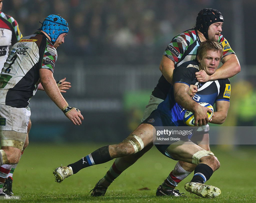 Simon Taylor of Bath is tackled by Mark Lambert of Harlequins as Joe Gray (L) looks on during the Aviva Premiership match between Bath and Harlequins at the Recreation Ground on November 23, 2012 in Bath, England.