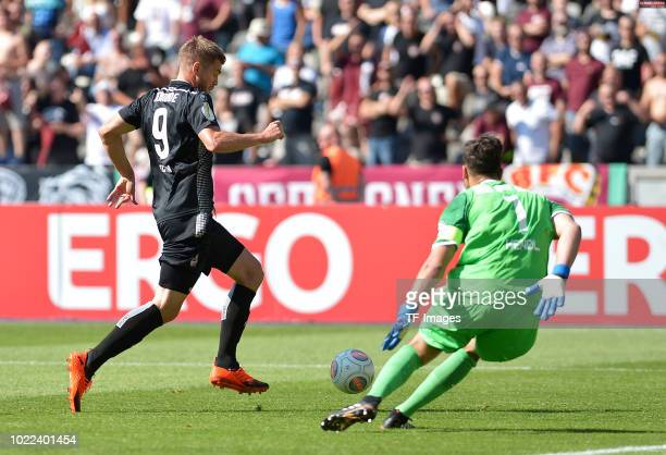 Simon Terodde of FC Koeln and Goalkeeper Bernhard Hendl of BFC Dynamo battle for the ball during the DFB Cup first round match between BFC Dynamo and...