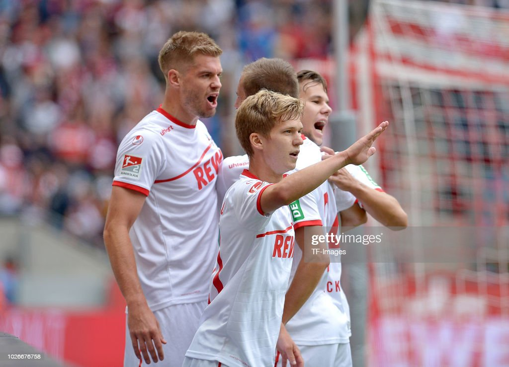 Simon Terodde of FC Koeln celebrates after scoring his team`s first goal with Vincent Koziello of FC Koeln, Louis Schaub of FC Koeln and Dominick Drexler of FC Koeln during the second Bundesliga match between FC Koeln and FC Erzgebirge Aue at RheinEnergieStadion on August 25, 2018 in Cologne, Germany.