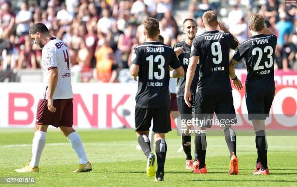 Simon Terodde of FC Koeln celebrates after scoring his team`s third goal with Louis Schaub of FC Koeln Dominick Drexler of FC Koeln and Jannes Horn...