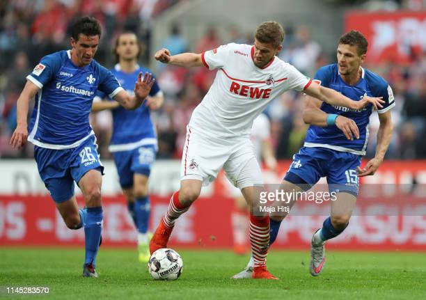 Simon Terodde of FC Koln takes on Christoph Moritz and Mathias Wittek of Darmstadt during the Second Bundesliga match between 1. FC Koeln and SV...