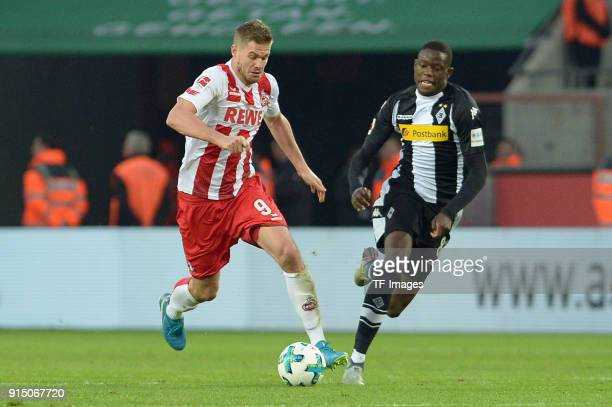 Simon Terodde of Koeln and Denis Zakaria of Moenchengladbach battle for the ball during the Bundesliga match between 1 FC Koeln and Borussia...
