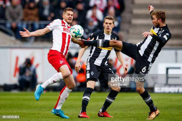Simon Terodde of Koeln is challenged by Christoph Kramer of Moenchengladbach during the Bundesliga match between 1 FC Koeln and Borussia...