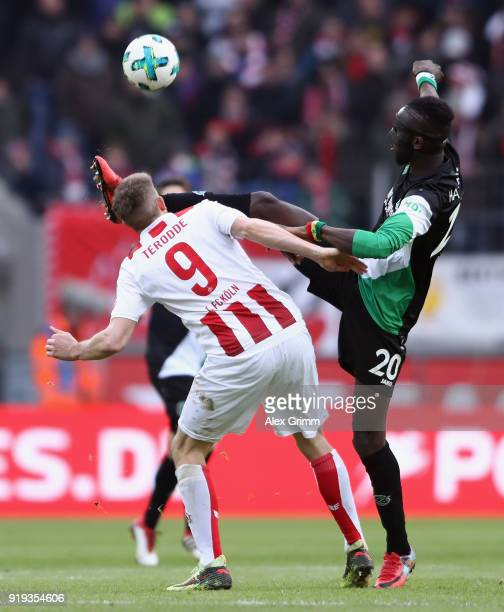 Simon Terodde of Koeln is hit by Salif Sane of Hannover during the Bundesliga match between 1 FC Koeln and Hannover 96 at RheinEnergieStadion on...
