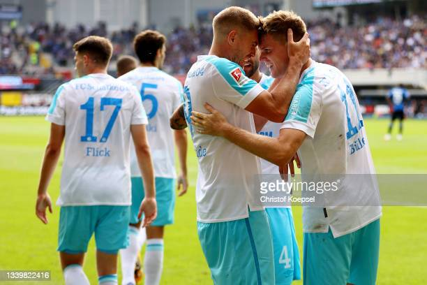 Simon Terodde of Schalke celebrates the first goal with Marius Buelter of Schalke during the Second Bundesliga match between SC Paderborn 07 and FC...