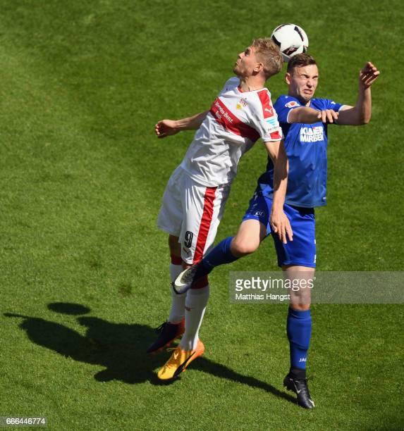 Simon Terodde of Stuttgart jumps for a header with Benedikt Gimber of Karlsruhe during the Second Bundesliga match between VfB Stuttgart and...