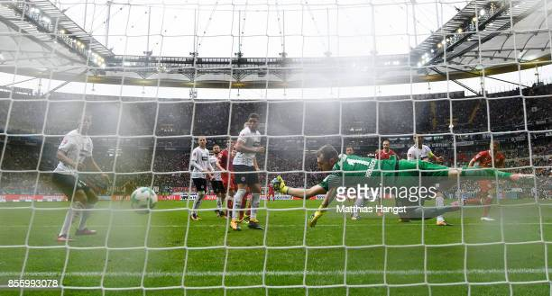 Simon Terodde of Stuttgart scores his team's first goal past goalkeeper Lukas Hradecky of Frankfurt during the Bundesliga match between Eintracht...