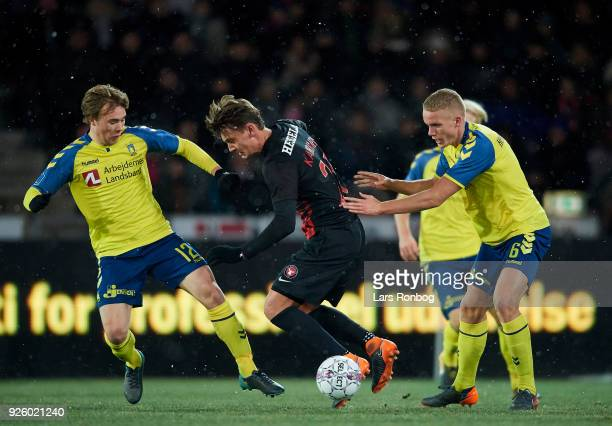 Simon Tibbling of Brondby IF Kaan Kairinen of FC Midtjylland and Hjortur Hermannsson of Brondby IF compete for the ball during the Danish Alka...