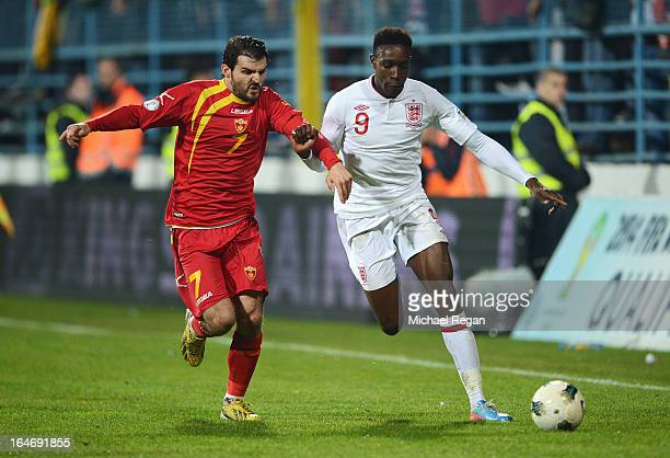 Simon Vukcevic of Montenegro battles with Danny Welbeck of England during the FIFA 2014 World Cup Qualifier Group H match between Montenegro and...