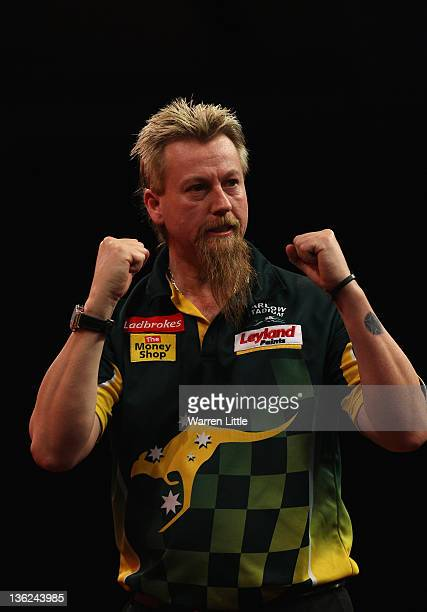 Simon Whitlock of Australia celebrates beating Michael van Gerwen of Holland during Day 12 of the 2012 Ladbrokescom World Darts Championship at...