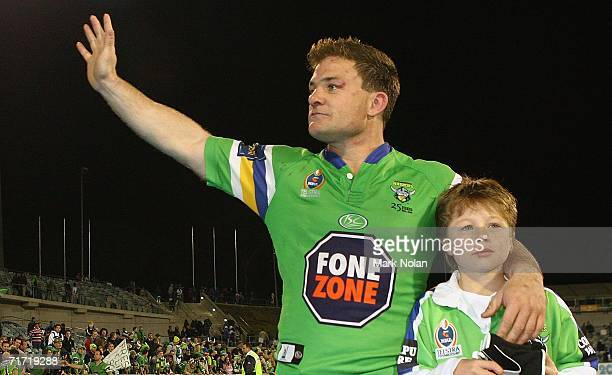 Simon Woolford of the Raiders farewells the Canberra crowd with his son after the round 25 NRL match between the Canberra Raiders and the Melbourne...