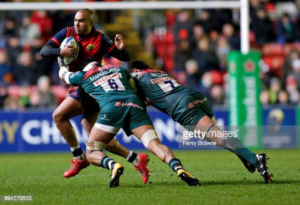 Simon Zebo of Munster tackled by Mike Williams and Tino Mapapalangi of Leicester Tigers during the European Rugby Champions Cup match between...