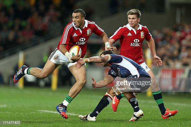 Simon Zebo of the Lions breaks a tackle during the International Tour Match between the Melbourne Rebels and the British Irish Lions at AAMI Park on...