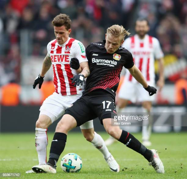 Simon Zoller of Koeln is challenged by Joel Pohjanpalo of Leverkusen during the Bundesliga match between 1 FC Koeln and Bayer 04 Leverkusen at...