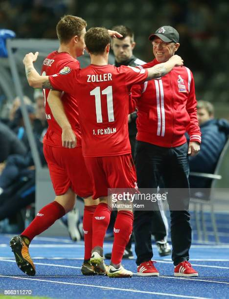 Simon Zoller of Koeln jubilates with team mates and head coach Peter Stoeger after scoring the first goal during the DFB Cup match between Hertha BSC...