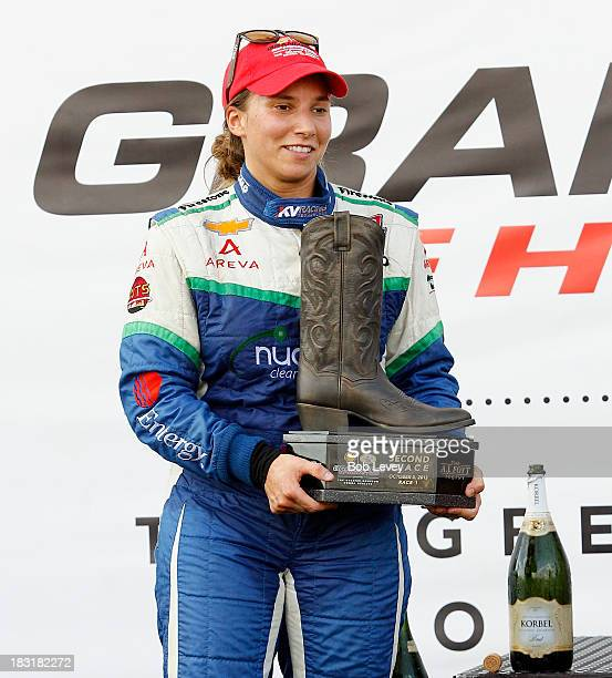 Simona De Silvesto driver of the KV Racing Technology car holds up the 2nd place trophy during the IZOD IndyCar Series Shell and Pennzoil Race 1 at...