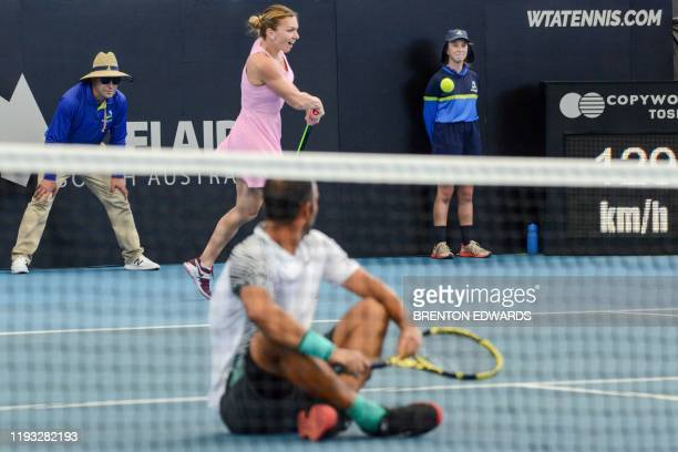 Simona Halep from Romania as partner Juan Sebastian Cabal of Colombia sits on the ground hits a return against Angelique Kerber of Germany and Robert...