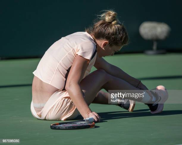Simona Halep from Romania falls to the ground and checks her ankle during her match against Ocean Dodin from France in their second round match...