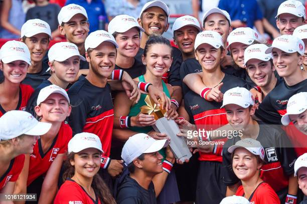 Simona Halep holds her trophy while surrounded by ball kids after the WTA Coupe Rogers final on August 12, 2018 at IGA Stadium in Montréal, QC