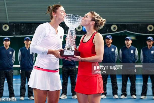 Simona Halep of Romania and IrinaCamelia Begu of Romania pose for photo with their doubles champion trophy after winning the final match against...