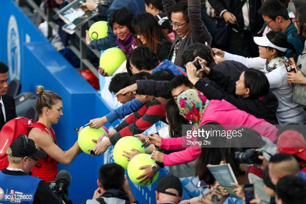 Simona Halep of Romania autographs for fans after winning the match against Aryna Sabalenka of Belarus during Day 5 of 2018 WTA Shenzhen Open at...