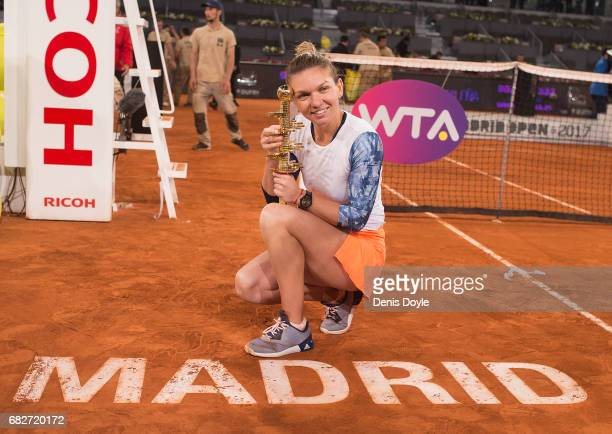 Simona Halep of Romania celebrates with the trophy after beating Kristina Mladenovic of France in their final match during day eight of the Mutua...