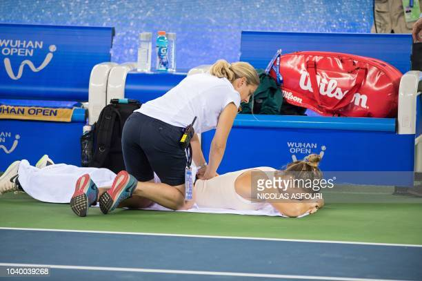 Simona Halep of Romania gets medical treatment as she plays against Dominika Cibulkova of Slovakia during their women's singles third round match of...