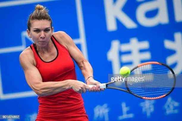 Simona Halep of Romania hits a return against compatriot Irina-Camelia Begu during their women's singles semi-final match at the WTA Shenzhen Open...