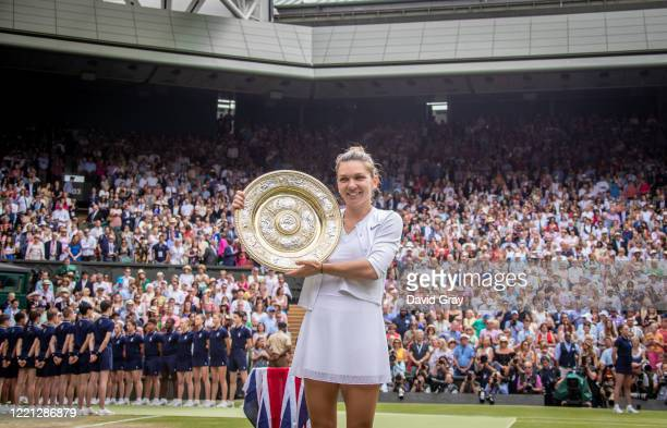Simona Halep of Romania holds the trophy after defeating Serena Williams of the United States in the Ladies Singles Final on Centre Court during the...