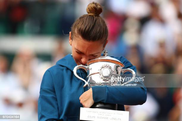 Simona Halep of Romania hugs the trophy as she celebrates victory following the ladies singles final against Sloane Stephens of The United States...