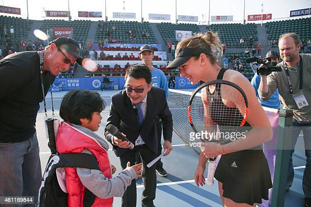 Simona Halep of Romania interacts with a young player after her match against Aleksandra Krunic of Republic of Serbia on day five of WTA Shenzhen...