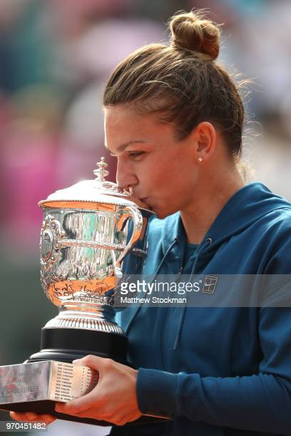 Simona Halep of Romania kisses the trophy as she celebrates victory following the ladies singles final against Sloane Stephens of The United States...