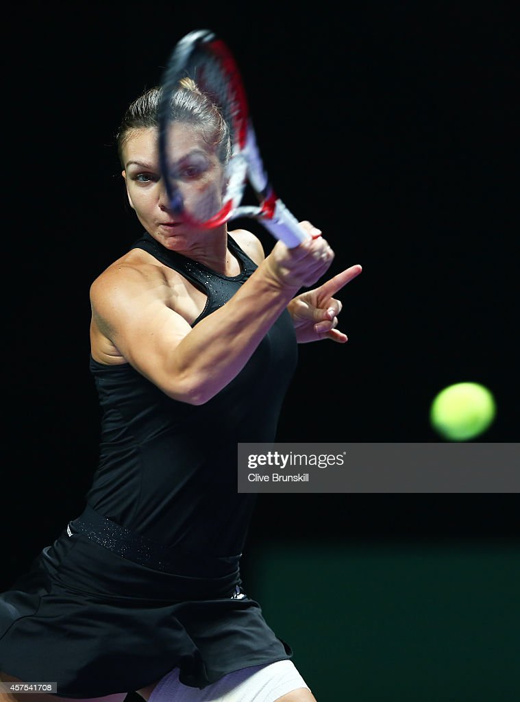Simona Halep of Romania plays a forehand against Eugenie Bouchard of Canada in their round robin match of the BNP Paribas WTA Finals at Singapore Sports Hub on October 20, 2014 in Singapore.
