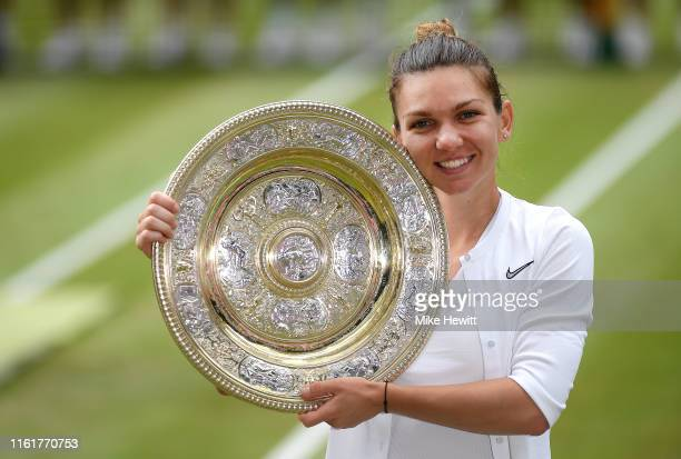 Simona Halep of Romania pose for a photo with her trophy after winning the Ladies' Singles final against Serena Williams of The United States during...