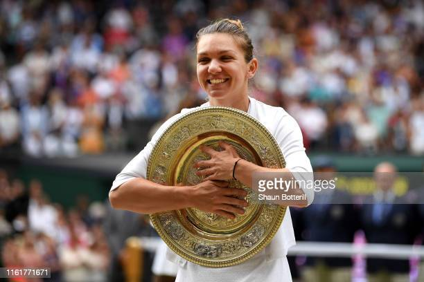 Simona Halep of Romania poses for a photo with the trophy after winning the Ladies' Singles final against Serena Williams of The United States during...