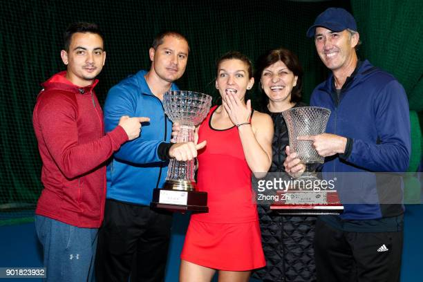 Simona Halep of Romania poses for photo with her Single's and Double's Champion trophies with her team during Day 7 of 2018 WTA Shenzhen Open at...