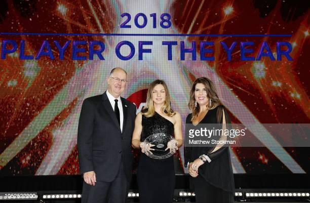 Simona Halep of Romania poses on stage with her Player of the Year award with Jennifer Capriati and Steve Simon CEO and Chairman of the WTA during...