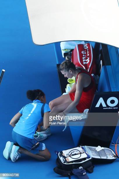 Simona Halep of Romania receives treatment after injuring her ankle in her first round match against Destanee Aiava of Australia on day two of the...