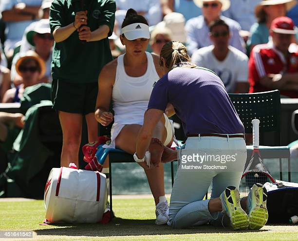 Simona Halep of Romania receives treatment from the trainer for an ankle injury during her Ladies' Singles semifinal match against Eugenie Bouchard...
