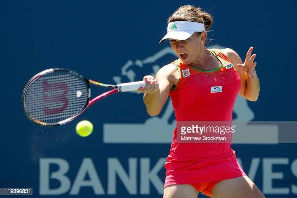 Simona Halep of Romania returns a shot to Sabine Lisicki of Germany during the Bank of the West Classic at the Taube Family Tennis Stadium on July 26...
